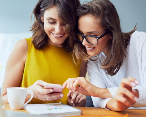 Female friends browsing internt on mobile phone