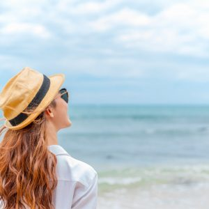 smiling young woman in sun hat on beach. summer, holidays, vacation, travel concept